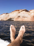 Mans Feet Hanging Over Side of Boat Stock Photos