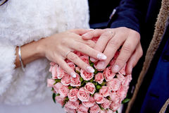 Mans and female hands on a bunch of flowers Stock Photography
