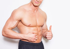 Man's fingers measuring her belly fat. Bodybuilder without shi Royalty Free Stock Photo
