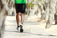 Mans foot running on the alley with trees alongside, focused on Stock Photo