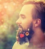 Mans framsida i profil med ett skägg med blommor hans skägg på naturlig bakgrund med bokeh Royaltyfri Bild