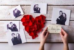 Mans händer Hans och hans flickvänfoto Rosa Petalhjärta Arkivbilder