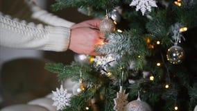 Mans händer sätter fejkar vita snö-flingor på en julgran i mörkt rum arkivfilmer