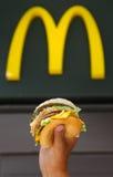 Mans händer som rymmer på en hamburgare Arkivfoto