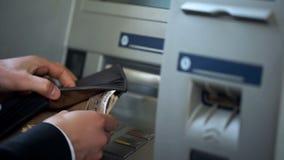 Mans händer som sätter den japanska yen i plånboken, kassa som återtas från ATM som reser royaltyfria bilder