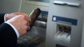Mans händer som sätter dollar i plånboken, kassa som återtas från ATM som utomlands reser arkivbilder