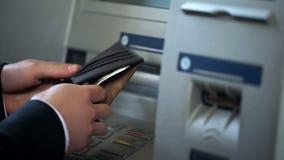 Mans händer som sätter ryska rubel i plånboken, kassa som återtas från ATM som reser arkivbilder