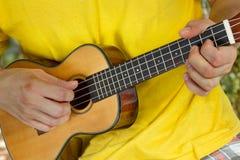 Mans händer som spelar ukulelet arkivfoton