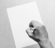 Mans hand with a ballpoint pen and blank white sheet of paper on a gray background, top view close-up. black and white photo. Mock up for text, congratulations Royalty Free Stock Photo
