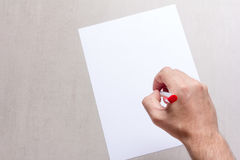 Mans hand with a ballpoint pen and blank white sheet of paper on a gray background, top view close-up. Mock up for text, congratulations, phrases, lettering Stock Image