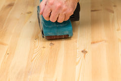 Mans hand on belt sander on pine wood Stock Photo