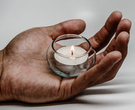 Mans hand and candlelight Stock Image