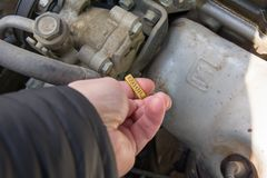 Mans hand check engine oil level check, dirty dust engine stock image