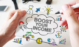 Mans hand drawing Boost Your Income concept on notebook Stock Photo