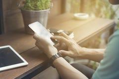mans hand genom att använda smartphonen med den digitala minnestavlan Arkivfoton