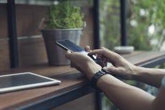 mans hand genom att använda smartphonen med den digitala minnestavlan Royaltyfri Foto