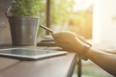 mans hand genom att använda smartphonen med den digitala minnestavlan Royaltyfri Bild
