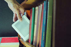Mans hand gets ebook among old books from the bookshelf. new tec. Mans hand gets ebook among old paper books from the bookshelf. new technology concept Royalty Free Stock Images