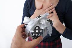 Mans hand giving a female present box Stock Photos