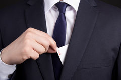 Mans hand hiding ace card in suit pocket Royalty Free Stock Photography