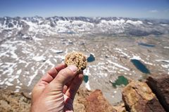 Hand Holding Cookie On Mountain Top Royalty Free Stock Image