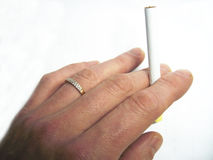 Mans hand holding cigarette in fingers isolated on the white background stock images