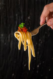 Mans hand holding a fork with pasta Royalty Free Stock Image
