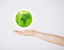 Mans hand holding green globe Royalty Free Stock Photography