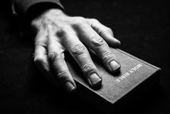 A mans hand on the Holy Bible. Royalty Free Stock Image