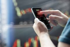 Mans hand holding mobile phone against dark stock market charts stock photography