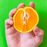 Mans hand holding an orange sliced in half Stock Photo