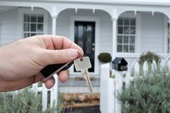 A mans hand holds a key against a house in Auckland New Zealand Royalty Free Stock Photo
