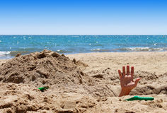 Mans hand out of the hole on the beach Royalty Free Stock Photography
