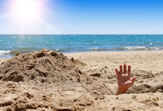 Mans hand out of the hole on the beach Stock Photography