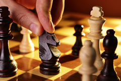 Mans hand playing a game of chess Royalty Free Stock Photos