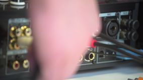 Mans hand plugging in dj audio mixing studio equipment. Close up of different colour plugs for power supply.