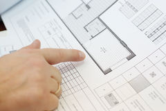Mans hand points at part of drawings of apartment Stock Image