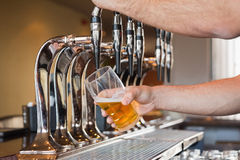 Mans hand pouring beer Stock Image