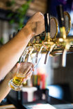 Mans hand pouring pint of beer behind the bar in pub stock images