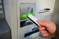 Man's hand puts credit card into ATM Royalty Free Stock Photo