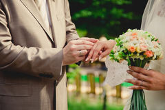 Mans hand putting a wedding ring on the brides Royalty Free Stock Images