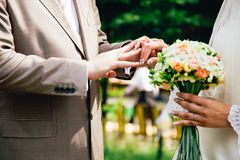 Mans hand putting a wedding ring on the brides Stock Image