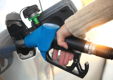Mans hand refilling the car with a gas pump Stock Photos