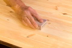 Mans hand on sanding block on pine wood Stock Photography