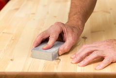 Mans hand on sanding block on pine wood Stock Photos