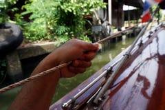 Mans hand som är hållande på repet royaltyfri foto