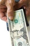 Mans hand som betalar dollarräkningen Arkivfoto