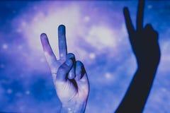 Mans hand som gör symbolet av seger och fred arkivbilder