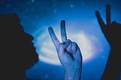 Mans hand som gör symbolet av seger och fred arkivfoto