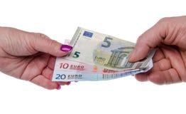 Mans hand som ger sedlar till en kvinnas hand Arkivbild